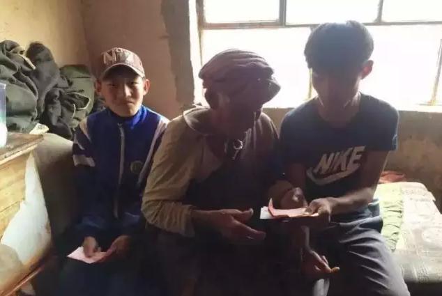 图为陈连平在青海省同德县唐古镇扎恤村为老人送去慰问金